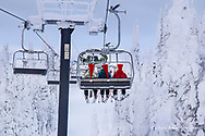 Skiers ride chairlift on Christmas at Whitefish Mountain Resort, Montana, USA