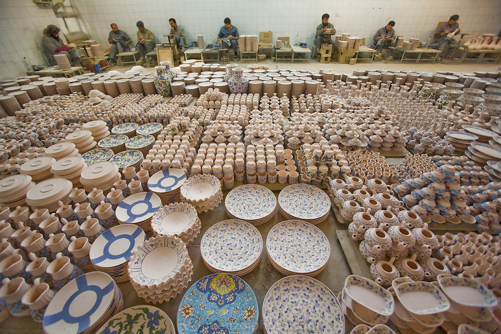 """Painters apply color to bisqueware at Morvarid (Pearl) pottery Factory, Meybod (Also spelled """"Maybod""""), Iran. Each of the painters applies an assigned traditional design."""