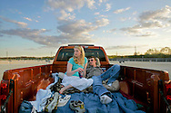 """Stephanie Malloy and Tom Nowak of Evergreen Park relax in a truck bed and listen to the Cubs game on the radio before the start of the movie """"The Benchwarmers"""" at the Cascade Drive-In in West Chicago."""