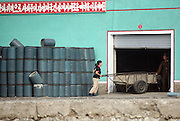 North Korean workers move equip,emt at a port in the town of Sunuiju on the DRPK-China border July 9, 2006. North Korea promised to use force against any country that tries to pressure it into a halt of its missile launches. DPRK, north korea, china, dandong, border, liaoning, democratic, people's, rebiblic, of, korea, nuclear, test, rice, japan, arms, race, weapons, stalinist, communist, kin jong il
