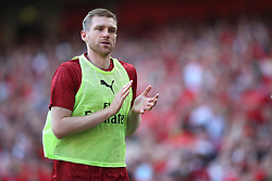 Arsenal's Per Mertesacker applauds the fans as he warms up on the touchline during the Premier League match at the Emirates Stadium, London.