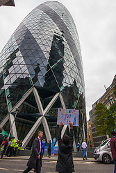 London, September 7th 2015. PICTURED: Young Joseph Demetriou, with a poster he made in support of his father's City Three Peaks Challenge, yells encouragement to his Dad Jimmy as he descends  from the top of the Gerkhin, the building he manages. The Outward Bound Trust City Three Peaks Challenge in conjunction with The Royal Navy and Royal Marines Charity is a breathtaking abseiling endeavour on the greatest urban mountain range: The City of London.