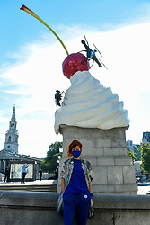 © Licensed to London News Pictures. 30/07/2020. LONDON, UK.  Artist Heather Phillipson poses in front of her sculpture 'THE END', which is unveiled to the public as the new Fourth Plinth artwork in Trafalgar Square.  THE END shows a giant swirl of replica whipped cream topped with a cherry, a fly and a drone.  Its drone transmits a live feed of the square which can be watched on a dedicated website.  The installation, originally planned for 26 March 2020 but postponed due to the coronavirus pandemic, will remain on display for the next year two years.  Photo credit: Stephen Chung/LNP