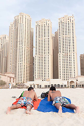 Tourists relaxing on beach at Jumeirah Beach resort district with high rise buildings to rear in Dubai, United Arab Emirates,UAE