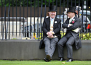 © licensed to London News Pictures. ASCOT, UK.  16/06/11. Two men sit on a wall. Ladies Day at Royal Ascot 16 June 2011. Royal Ascot has established itself as a national institution and the centrepiece of the British social calendar as well as being a stage for the best racehorses in the world. Mandatory Credit Stephen Simpson/LNP