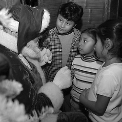 Santa Claus talks with children at the annual Miramar Restaurant Christmas party on Monday, Dec. 20, 2004 in Half Moon Bay. Russell Bissonnette has performed at the party for 15 years. The Miramar is located in Half Moon Bay just off of Coastal Highway 1 on the waterfront...Photo by David Calvert<br />