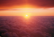 Sunset from airplane window over the clouds