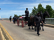 7/26/2020 SELMA Alabama A horse drawn carriage from Watkins Funeral Home in Atlanta leads the flag draped casket of Civil Rights icon and Congressman John Lewis over the Edmund Pettus Bridge for the last time.The rose petals represent the blood shed from Bloody Sunday in 1965 where Lewis was beaten by police and ended up with a  fractured skull. On the anniversary of President Lyndon Johnson signing the Voting Rights Act, Congressman John Lewis's casket is pulled by a horse drawn carriage  across the Edmund Pettus Bridge in Selma for the last time. The casket is headed to the State Capitol in Montgomery where he will lay in state and then will head to Washington DC and then to his final resting place in Atlanta Georgia.  Photo© Suzi Altman