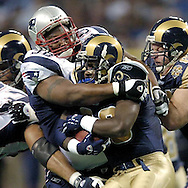 New England Patriots defensive tackle Keith Traylor (98) wraps up St. Louis Rams running back Marshall Faulk (28) for no gain, during the first quarter of the Patriots 40-22 win in St. Louis, Missouri, November 7, 2004.