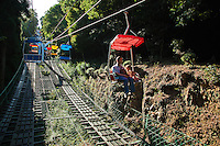 Mt Takao Chair lifts -  You step onto the moving walkway, the chair looms up behind you, and you fall back into it.  There is no safety rail at the front of the chair but there is netting below the chair lift on the high bits so that if you fall you won't fall too far.