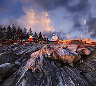 A Stormy Sunset Casts Dramatic Light Over The Rugged Sea Coast At The Foot Of The Pemaquid Point Lighthouse, Bristol Maine, USA