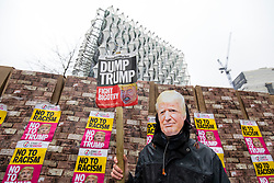 © Licensed to London News Pictures. 20/01/2018. London, UK. A protester wearing a Donald Trump mask stands next to a model of the proposed border wall outside the new American Embassy in Nine Elms on the first anniversary of Trump's inauguration as US President. Trump has cancelled his planned February 2018 visit to the UK and has described the new embassy as a 'bad deal'. Photo credit: Rob Pinney/LNP