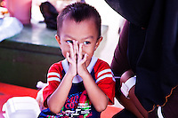 Little boy with his hands up over his face