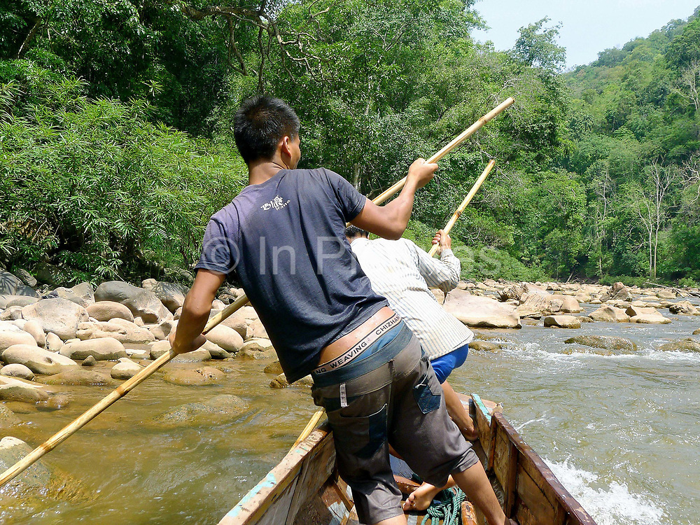 Boatmen Savath and Sengkham navigate their boat up the rapids using bamboo poles on the Nam Ou river during the dry season when the river level is low, Phongsaly province, Lao PDR. The Nam Ou river connects small riverside villages and provides the rural population with food for fishing. But this river and others like it, that are the lifeline of rural communities and local economies are being blocked, diverted and decimated by dams. The Lao government hopes to transform the country into 'the battery of Southeast Asia' by exporting the power to Thailand and Vietnam.