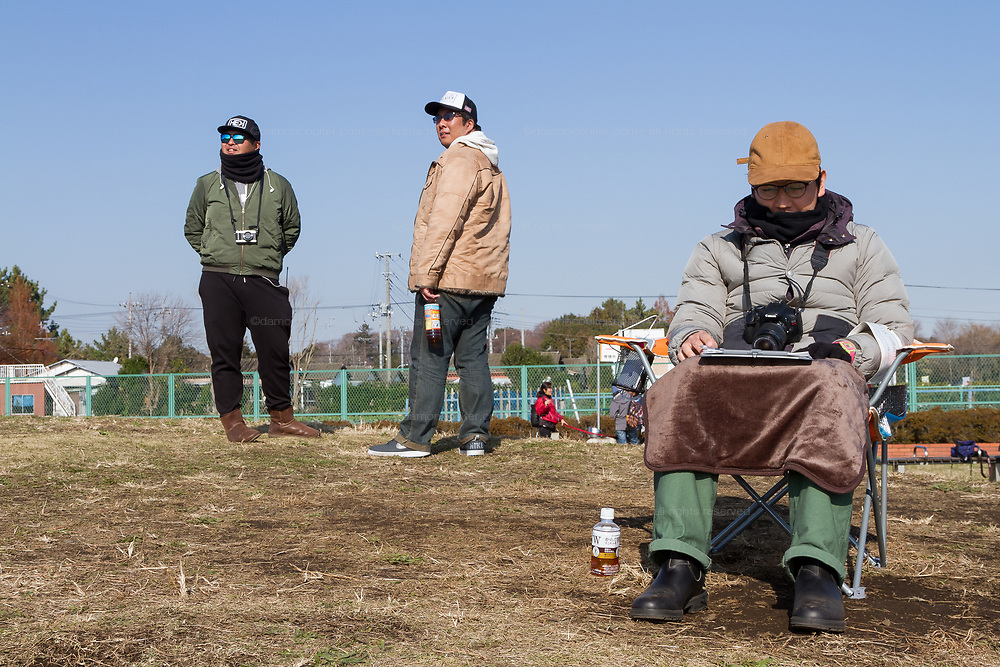 Military aircraft enthusiasts keep watch on the sky while Masa Hayashi (seated right)  records flight times and type of aircraft to analyse engineering effects and noise levels in a park at the end of Atsugi Airbase runway,Yamato, Kanagawa, Japan. Friday December 21st 2018