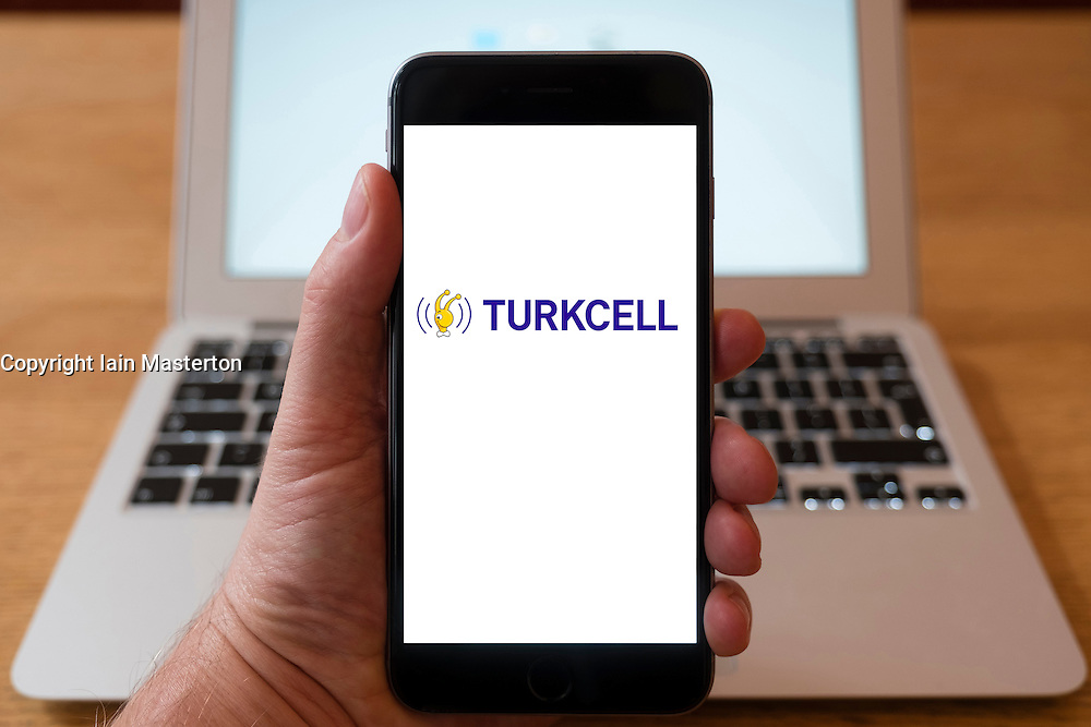 Using iPhone smartphone to display logo of Turkcell,, Turkeys leading mobile phone operator