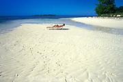 visitor enjoying the sun at <br /> West End Beach, Walker's Cay, <br /> Bahamas ( Western Atlantic Ocean ) MR 89