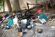 Cuban man homeless sat in his makeshift home, pots pans and reclaiming household items, cooking, next to the river in a park, Havana.