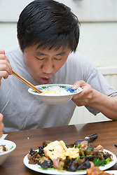 Man eating from a bowl of rice using chopsticks,