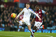 Jamie Vardy of Leicester city (l) gets away from Jores Okore of Aston Villa and attempts to chip the keeper which leads to the opening goal. . Barclays Premier league match, Aston Villa v Leicester city at Villa Park in Birmingham, The Midlands on Saturday 16th January 2016.<br /> pic by Andrew Orchard, Andrew Orchard sports photography.
