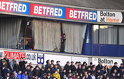 A fan peaks through the curtains in one of the director boxes during the game