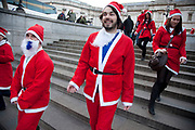 London, UK. Sunday 9th December 2012. A flash mob of Santas descends on Trafalgar Square. Christmas celebrated here with the annual Santa Pub Crawl party visiting the famous pubs & sights of London with everyone decked out in jolly red Santa suits. Organised by Fanatics, an Australian sports and party company.