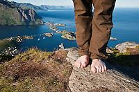 Man stands barefooted on rock on Reinebringen, Reine, Lofoten islands, Norway