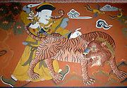Mural painting of a Mongol with a chained tiger symbolising the supremacy of the Mongolian yellow hat buddhists over the Tibetan  red hat buddhists in Bhutan.  Paro Dzong, Druk Yul,  Bhutan. 10 November 2007