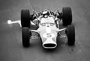 """JIMMY FLYING UNDER THE FLYING BRIDGE, USGP 1967<br /> Jim Clark, Lotus 49, at Watkins Glen, NY; photo by Pete Lyons<br /> <br /> GRACE AT SPEED ... To my eye, one of F1's most aesthetically beautiful periods came just before wings, when designers attained the final expression of their age-old conception of car-as-projectile, a bullet to pierce the air, not wedge itself under it. And among the most satisfying of these was Colin Chapman's Lotus-Ford Cosworth 49. Slim, tidy, deceptively simple-looking, it was a perfect marriage of slender aluminum monocoque with compact V8 — the engine was in fact the rear of the chassis, an elegant engineering solution that would catch fire throughout the racing industry.<br /> <br /> One of the vantage points from which you could best perceive the 49's beauty was the old """"flying bridge"""" at Watkins Glen, a gantry platform cantilevered out over the start-finish line (see photo below). It was meant for flaggers and officials, but sometimes pushy photographers could talk their way up there too, and I used to squeeze in as often as I could. From there you enjoyed a viewpoint that was as rare then as it is now.<br /> <br /> Of all the places from which I used to shoot at the old home of the US Grand Prix, for me the """"bridge"""" is the one that most clearly says """"The Glen."""""""