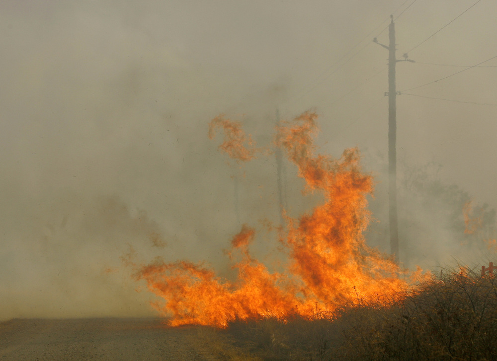 Photo © 2005 Alex Jones..Flames from a massive grass fire approach a county road North of Cross Plains on the afternoon of Tuesday, December 27, 2005.