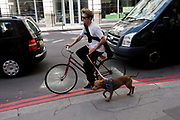 An urban cyclist tows pedals down a City of London street alongside his running pet dog on lead in London Street. Sandwiched between traffic which are queuing on this red route on Bishopsgate, an ancient highway now in the capital's financial centre, the young man is on a ladies' bike and holds on to his animal using a red lead.