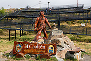 """Sign for El Chalten mountain resort, with carved wood mountaineer, Santa Cruz Province, Argentina, Patagonia, South America. A wheelchair ramp ascends a small hill in the background. The village is settled on the riverside of Rio de las Vueltas, within Los Glaciares National Park near the base of Cerro Fitz Roy (3405 m or 11,171 ft elevation), at the edge of the Southern Patagonian Ice Field. The town is 220 km north of El Calafate. Chaltén comes from a Tehuelche word meaning """"smoking mountain"""", due to clouds that usually form over Monte Fitz Roy."""