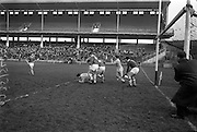 """05/02/1967<br /> 02/05/1967<br /> 5 February 1967<br /> National Hurling League: Cork v Dublin at Croke Park, Dublin. <br /> Dublin's H. Kinsella (15) falls on the ball as Cork backs, J. O'Leary (4), P. Doolan (2), and T. O'Donoghue (hidden) try to extricate the ball while Cork goalie, P. Barry (right), anxiously awaits the outcome. The result of the incident was a """"free in"""" for Dublin, who then scored a point."""