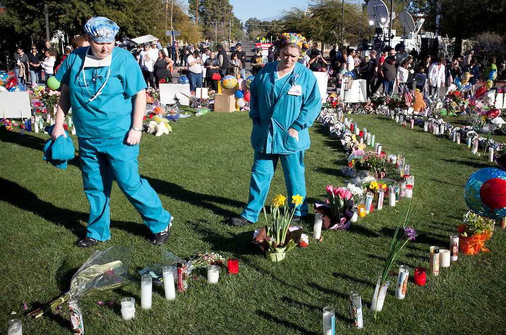 """University Medical Center nurses, who didn't want to be identified, visit a makeshift memorial for U.S. Rep. Gabrielle Giffords and the other victims of the Jan. 8 mass shooting.  President Barack Obama attended, the """"Together We Thrive: Tucson and America"""" later the same day.  Many struggle to understand the lenient attitudes toward guns in the Grand Canyon State, after the shooting Jan. 8 that killed six people and wounded 13, including Giffords.  Jared Loughner, the 22-year-old man accused of committing the crimes with a Glock 9 mm with an extended magazine, has been deemed mentally unfit to stand trial."""