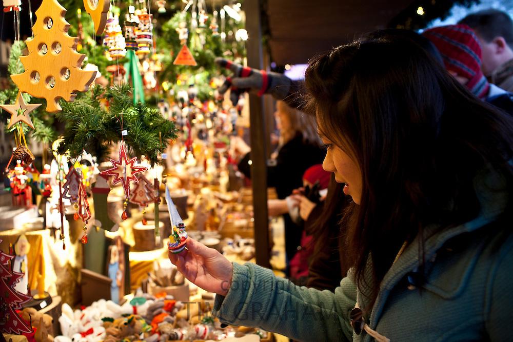 Customer shopping for Christmas ornaments at Christmas market, Winter Wonderland, in Hyde Park, London
