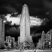 """The Flatiron Building, is a triangular 22-story steel-framed landmarked building located at 175 Fifth Avenue in Manhattan, New York City, and is considered to be a groundbreaking skyscraper. Upon completion in 1902, it was one of the tallest buildings in the city at 20 floors high and one of only two skyscrapers north of 14th Street – the other being the Metropolitan Life Insurance Company Tower, one block east. The building sits on a triangular block formed by Fifth Avenue, Broadway, and East 22nd Street, with 23rd Street grazing the triangle's northern (uptown) peak. As with numerous other wedge-shaped buildings, the name """"Flatiron"""" derives from its resemblance to a cast-iron clothes iron.<br /> <br /> The building, which has been called """"one of the world's most iconic skyscrapers and a quintessential symbol of New York City"""",anchors the south (downtown) end of Madison Square and the north (uptown) end of the Ladies' Mile Historic District. The neighborhood around it is called the Flatiron District after its signature building, which has become an icon of New York City.<br /> <br /> The Flatiron Building was designated a New York City landmark in 1966,added to the National Register of Historic Places in 1979, and designated a National Historic Landmark in 1989."""