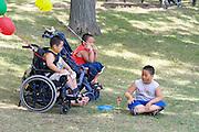 Handicapped Asian boys enjoying a moment in the shade. Dragon Festival Lake Phalen Park St Paul Minnesota USA