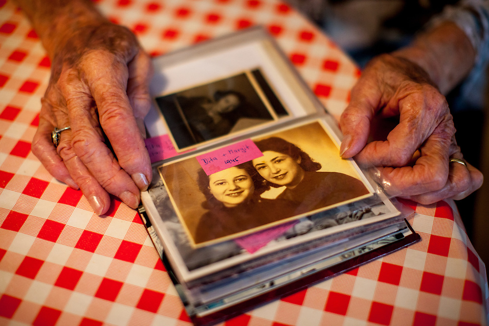 """Dita Kraus with a photo album from the past (the image shows Dita with her friend Margit Barnai in 1945) in her flat in Prague Vinohrady. Born in Prague to a Jewish family in 1929, Dita Kraus has lived through the most turbulent decades of the twentieth and early twenty-first centuries. Here, Dita writes in her book """"A Delayed Life: The true story of the Librarian of Auschwitz"""" with startling clarity on the horrors and joys of a life delayed by the Holocaust. From her earliest memories and childhood friendships in Prague before the war, to the Nazi-occupation that saw her and her family sent to the Jewish ghetto at Terezín, to the unimaginable fear and bravery of her imprisonment in Auschwitz and Bergen-Belsen, and life after liberation."""