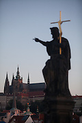 Statue of St. John the Baptist with golden cross at Charles Bridge during early morning. In the back St. Vitus Cathedral and Prague Castle.
