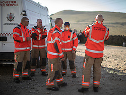 "© Licensed to London News Pictures . 28/06/2018 . Saddleworth , UK . Firefighters at Higher Swineshaw Reservoir . The army are being called in to support fire-fighters , who continue to work to contain large wildfires spreading across Saddleworth Moor and affecting people across Manchester and surrounding towns . Very high temperatures , winds and dry peat are hampering efforts to contain the fire , described as "" unprecedented "" by police and reported to be the largest in living memory . Photo credit: Joel Goodman/LNP"