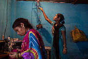 Poonam's older sister Jyoti, 14, (right) is reaching for electrical wires in order to start the family's small fan while their mother is busy mending some clothes with a sewing machine inside their newly built home in Oriya Basti, one of the water-contaminated colonies in Bhopal, Madhya Pradesh, India, near the abandoned Union Carbide (now DOW Chemical) industrial complex.