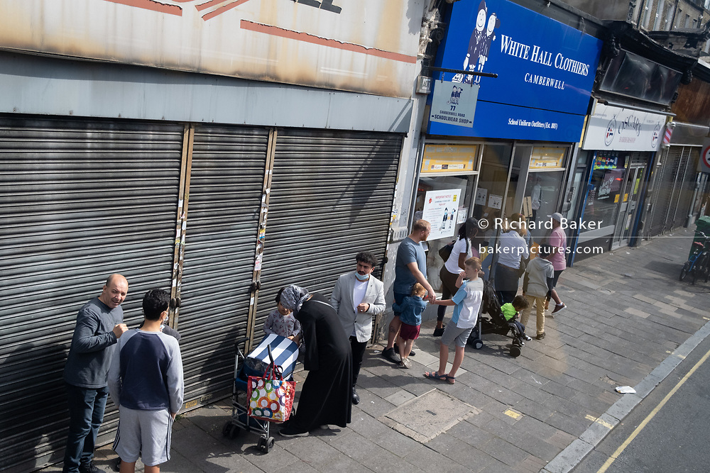 Ad the new school term restarts in England, and after the long closure during the Coronavirus pandemic, shoppers queue outside the school  unirom outfitters 'White Hall Clothiers' (established in1883) on the Walworth Road in Camberwell, on 1st September 2020, in London, England.
