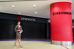 © Licensed to London News Pictures. 23/06/2020. London, UK. A woman walks past 'CINEWORLD' in Wood Green, north London, which has been closed since 23 March following the COVID-19 lockdown. Cinemas, museums and galleries will re-open from 4 July as Prime Minister Boris Johnson outlines the plans to restore normal life after three months of coronavirus lockdown. Photo credit: Dinendra Haria/LNP