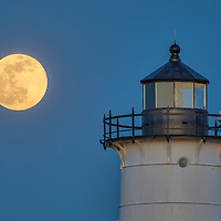 Pink full moon rising behind Nobska Light in Falmouth, Massachusetts on Cape Cod.