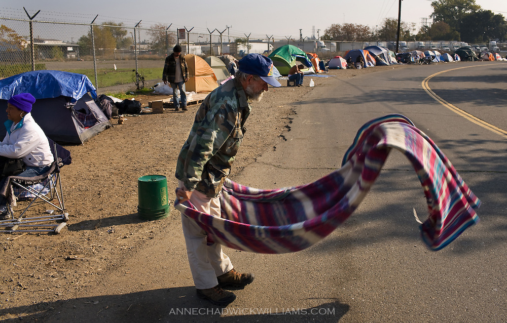 Homeless Tony Sims, 51, shakes out a blanket on Bannon St. on November 23, 2008 where he has been camping since August along with about a hundred others. On November 24, police moved all the homeless off Bannon St. in the constant chess game that is played with this population.