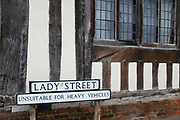 An 'Unsuitable for Heavy Vehicles' traffic sign outside the window of a medieval house on Lady Street, Lavenham, on 9th July 2020, in Lavenham, Suffolk, England. By the late 15th century, the town was among the richest in the British Isles, paying more in taxation than considerably larger towns such as York and Lincoln. Several merchant families emerged, the most successful of which was the Spring family. Heavy traffic is a problem now for small villages dissected by A and B-Roads throughout rural Britain.  The wool trade was already present by the 13th century, steadily expanding as demand grew. By the 1470s Suffolk produced more cloth than any other county.
