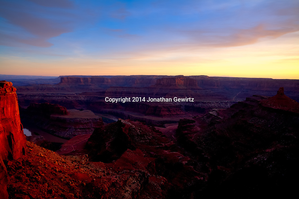 Warm light from the setting sun highlights Dead Horse Point over the Colorado River near Moab, Utah.<br /> <br /> WATERMARKS WILL NOT APPEAR ON PRINTS OR LICENSED IMAGES.