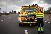 """A Highways England enforcement officer stops all traffic using a """"DO NOT PASS' sign on the south bound lane of the M1 motorway somewhere near Loughborough so that her colleagues can safely remove a broken down vehicle from the carriageway on the 29th of April 2021, United Kingdom. Highways officers patrol motorways to ease congestion and ensure the roads are safe and efficient for all users."""