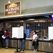 CHARLOTTE, NC - OCT 15: Voting booths are seen set up in front of a concession stand inside the Spectrum Center on the first day of early voting in Charlotte, North Carolina on October 15, 2020.  Many large sporting venues in the city offered their buildings for early voting  to allow greating social distancing for voters and volunteers. Polling locations have also been retrofit with extra personal protective equipment to combat the spread of COVID-19 while early voting in the state of North Carolina runs from October 15th to October 31st. (Photo by Logan Cyrus for The Washington Post)