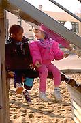 Friends age 4 talking on school yard playground.  St Paul  Minnesota USA